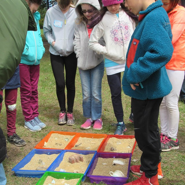 A group of students surround and look at sand in colorful trays.