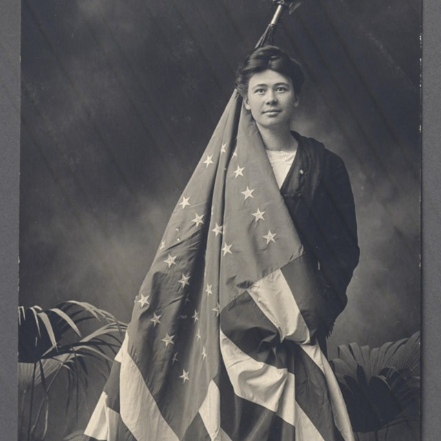 A women poses for a photograph holding an American flag that is draped around her body.