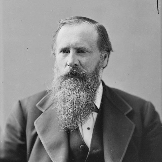 A portrait photograph of a man with a long beard.