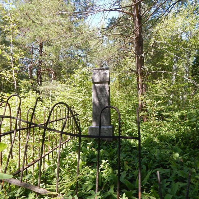 A grave marker is surrounded by a dilapidated fence in the forest.