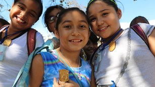 Four girls look proud wearing their Junior Ranger badge.