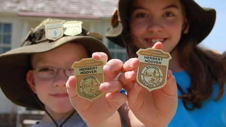 Two kids hold up Junior Ranger badges from Herbert Hoover National Historic Site