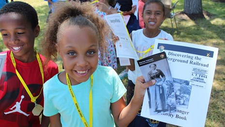 Several kids hold up junior ranger program materials