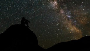 A person sits on a large rock gazing at a multitude of stars