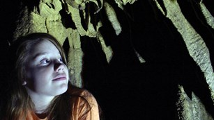 Girl in orange shirt looks up and shadows on the wall of a cave.