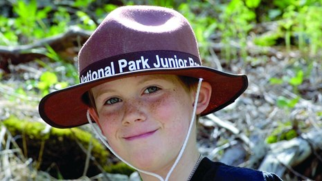 Boy wearing a brown hat with the words, Junior Ranger.