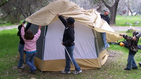 Parents and kids put a roof over their tent.