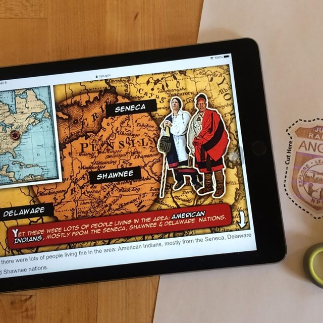 An iPad displays a comic book style online junior ranger activity with printed badge and scissors.