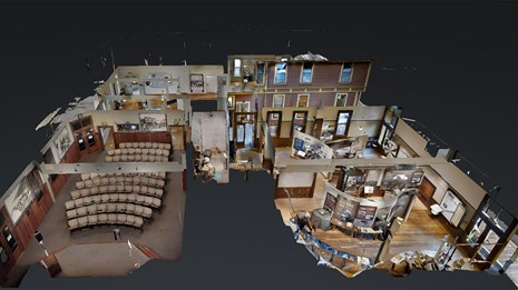 Dollhouse view of large building with five rooms filled with exhibits and one with theater seats.