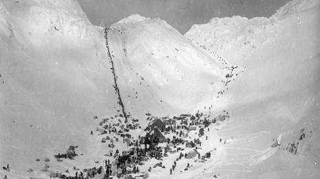 Black and white photo of people gathered in a flat area before a steep line ascends a snowy pass.