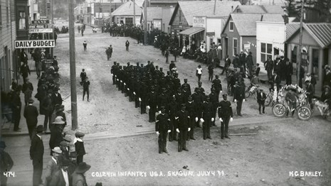 Formation of soldiers standing at attention in a street with onlookers.