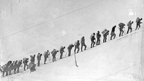 Black and white photo of people standing in a line on a snowy slope.