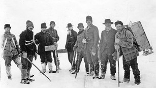Black and white photo of 9 bundled men standing at the Alaska-British Columbia border in the snow.