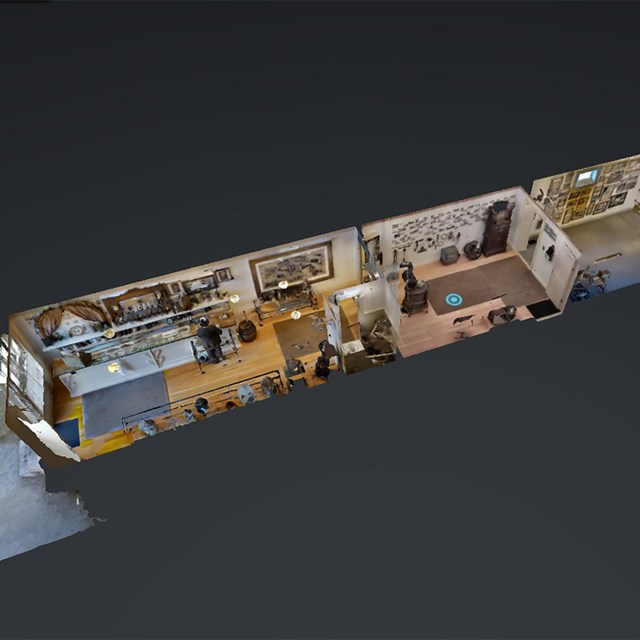 Dollhouse view of a long narrow building with three rooms and lots of furnishings