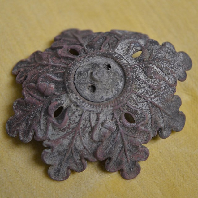 Metal object decorated with oak leaves