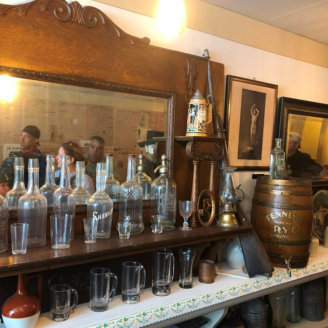 Bottles, glasses, and other items line an old back bar with a mirror behind them