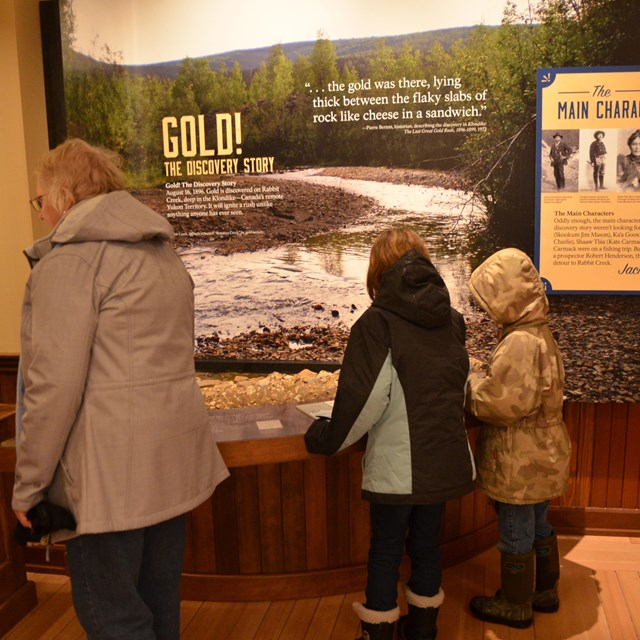 An adult and two children look at an exhibit about gold discovery
