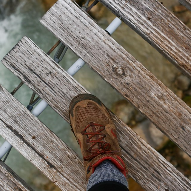 Hiking boot on bridge with river below