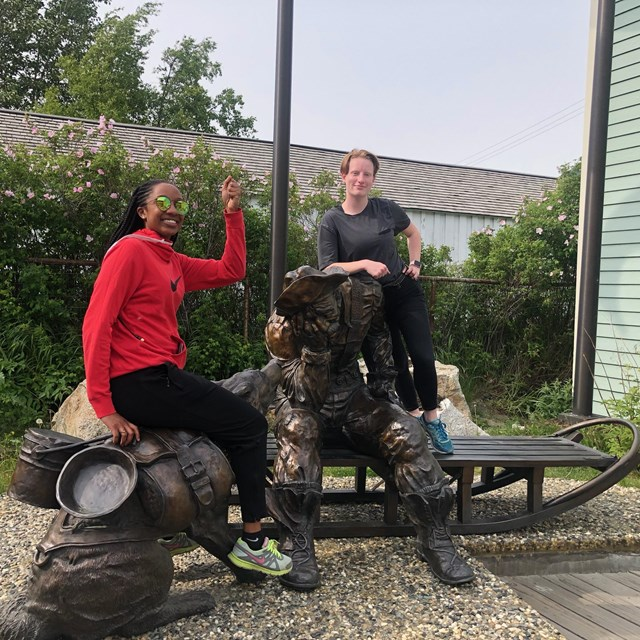 Two women sit on a bronze statue of a man seated on a sled and his dog