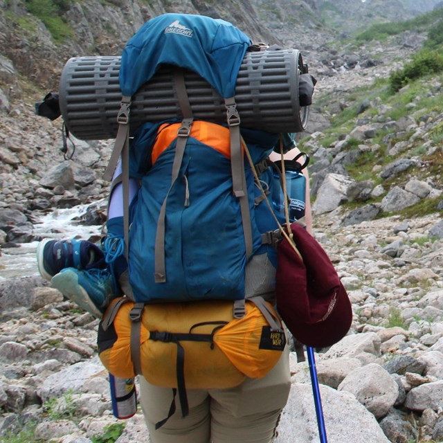 A backpacker hikes on rocky terrain