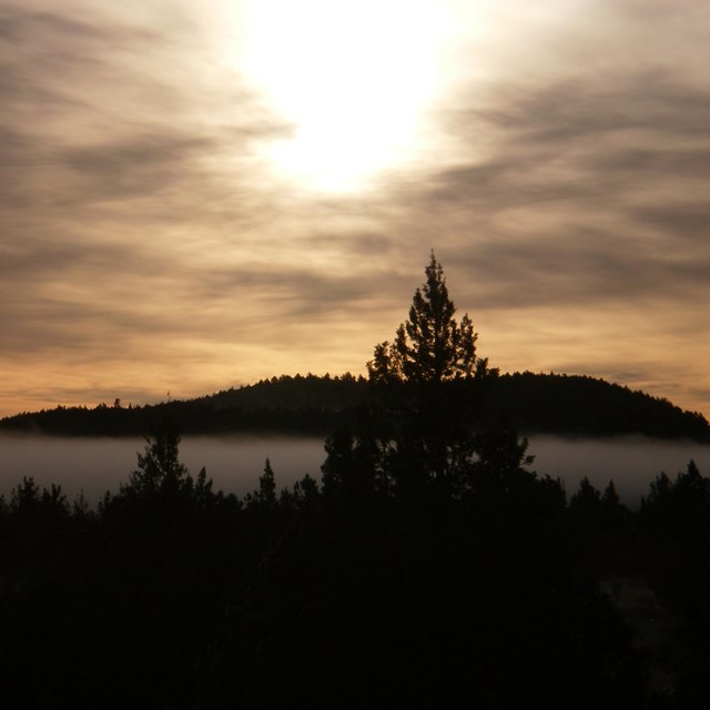 Sunset in cloudy sky over mountain and trees at Lava Beds National Monument