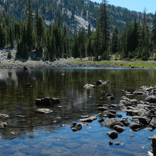 Shallow lake in Lassen Volcanic NP with rocks in foreground and trees and cliff along the shore