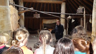 6 students listen to a female ranger's presentation inside an earthlodge.