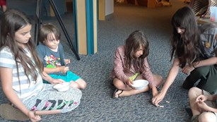 4 kids and female ranger sit in circle on floor playing a game with bowls, sticks, and wooden chips.