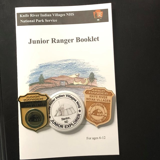 Jr Ranger booklet with three badges on it.