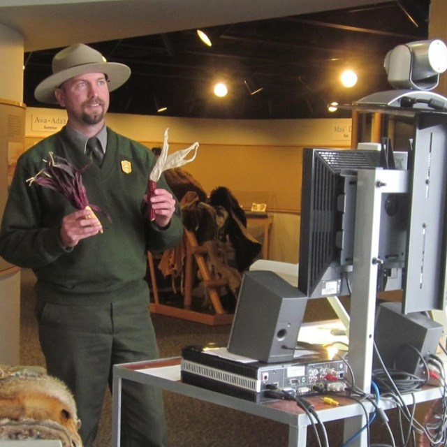 Male ranger holds 2 objects while looking at a tv monitor.