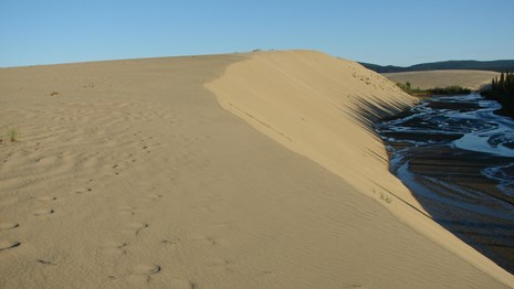 sand dunes with creek on right side