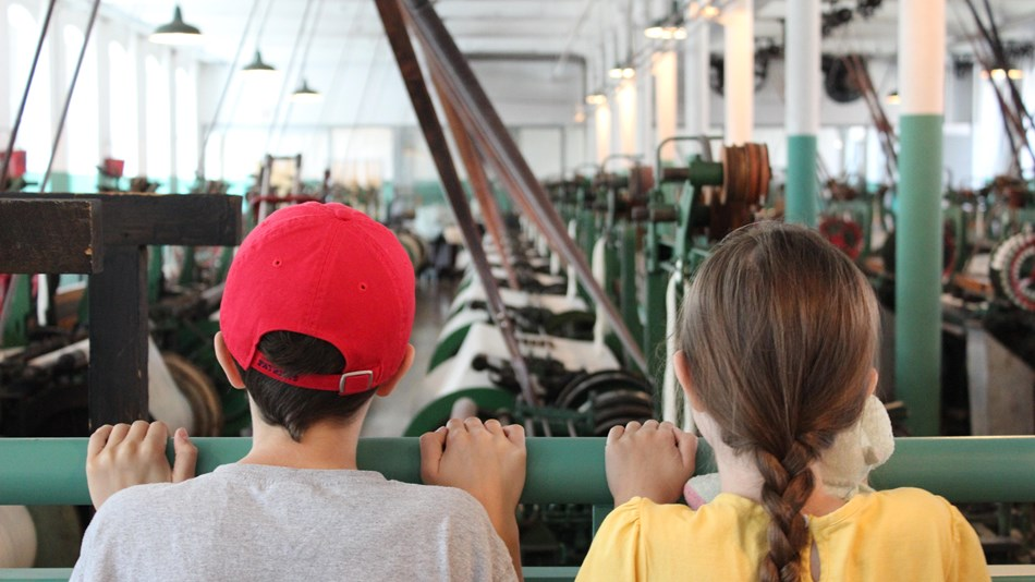 Two kids looking at recreation of a 1910s mill weaving room.