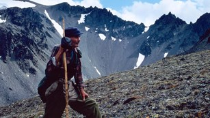 Photo of a man with a tall walking stick standing in alpine tundra with jagged mountains behind him.
