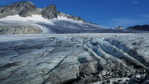 The surface of a glacier with a mountain peak rising in the back