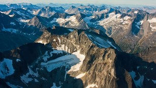 An aerial view of jagged rust-colored mountains