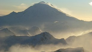 Mist rises from ridges leading to the Redoubt Volcano