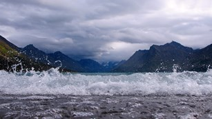 Waves break on a beach with mountains over water