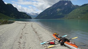 A kayak on a sandy beach next to a lake