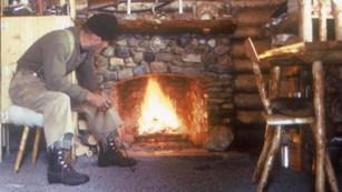 Image of a man in front of a fireplace in a log cabin.