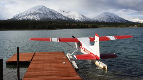 A floatplane parked at a dock in Port Alsworth