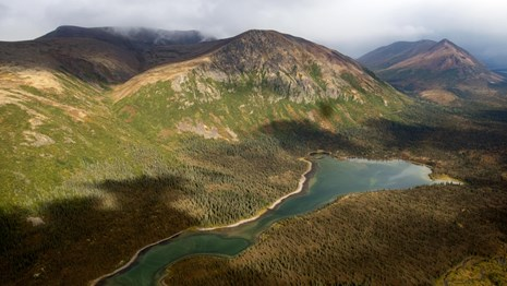 Aerial image of a lake in a valley with mountains in the background.