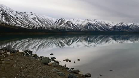 Image of snow capped mountains with lake shore in foreground.
