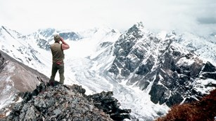 Vintage photo of a man looking across a glaciated mountain valley with binoculars.