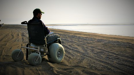 a man sitting in a dune buggy wheelchair on the beach