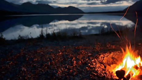 Photo of a campfire near a lake at dusk.