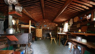 Photo of the interior of a small, one room log cabin filled with rustic items..