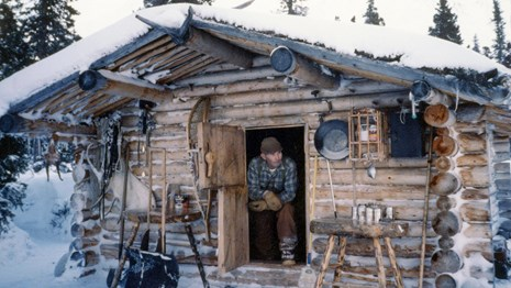 Man wearing blue flannel shirt and brown pants sits in open doorway of a log cabin on a winter day.