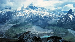 photo of a glaciated volcano with alpine tundra and a river valley in the foreground.