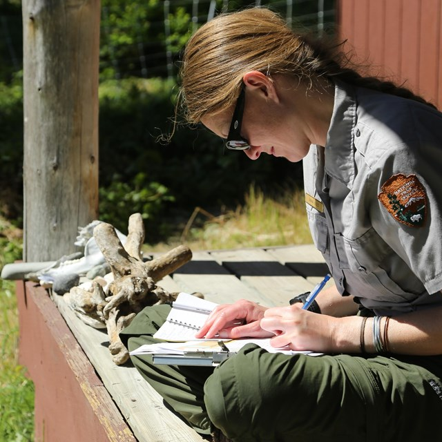 A female park ranger writes in a journal on a cabin porch