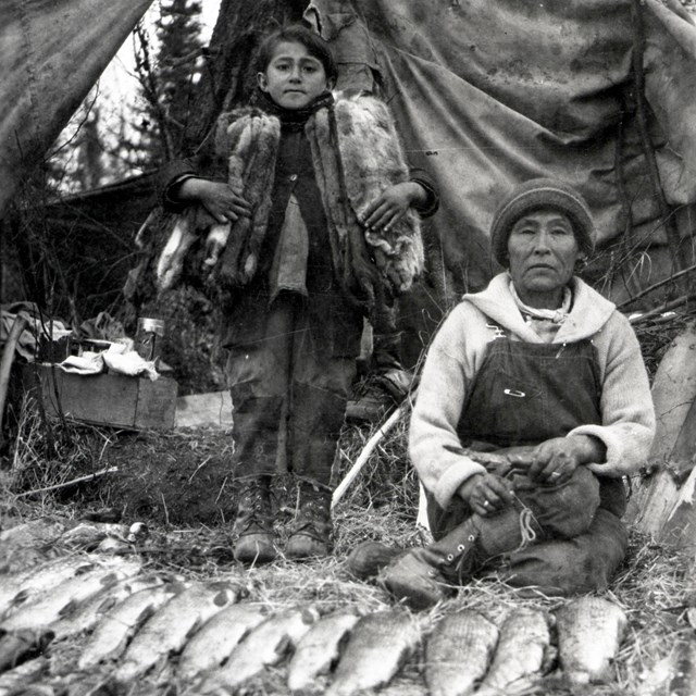 Woman and child in front of tent with fish and furs in foreground.